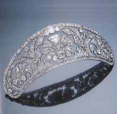 A Belle Epoque diamond diadem, circa 1910. The tapering band of openwork design, the centre bearing a fan-shaped motif within an open foliate border, decorated with two similar smaller motifs at each side, with floral and foliate clusters in between, set throughout with cushion-shaped diamonds. Sotheby's Magnificent Jewels, St. Moritz, 22 February 1997.