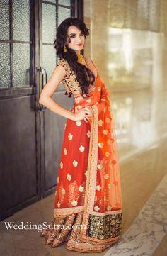 An orange Lehenga Saree with Gold embroidery and a contrasting Green border by Sabyasachi at WeddingSutra on Location. #weddingsutra #bridallehenga #lehenga #Indianbride #Indianoutfit #bridallook #weddingideas #orange #gold #sabyasachi