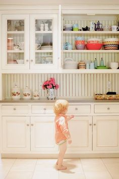 design - build - remodel with open shelves to help conserve hardwood trees for future generations.  fun colorful dishes in a white kitchen -  cheerful!
