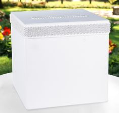 This beautiful Bling Card Box will certainly attract your guests attention!  Card box is covered in white satin and features white satin ribbon and sparkling faux rhinestone embellishments.  The slotted lid opens for easily retrieving cards.