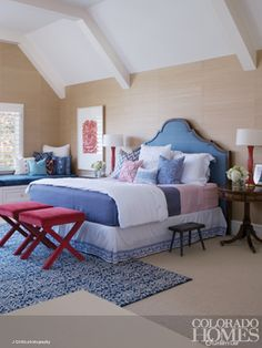 This master bedroom is elegant yet casual. The bed, with its pretty upholstered headboard and casual linens, takes center stage, while classic side tables, modern lamps and fun benches continue the home's eclectic, not-so-serious style. Rich grasscloth wallpaper and a Karin Schminke print add warmth to the space, with the help of a fireplace opposite the bed. Photo by J Curtis for @Colorado Homes & Lifestyles, http://coloradohomesmag.com