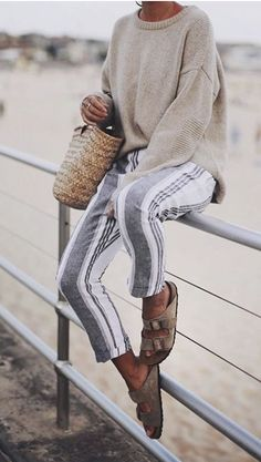 Such a cozy beach outfit! Grey and white striped linen pants, Birkenstock sandals, an oversized knit sweater, and that bag-- all she needs is a cup of tea.