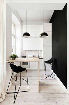 In deze kleine keuken worden lichte kleuren gecombineerd met zwart.