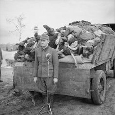 Oberleutnant F Hosler an SS officer at the camp stands by a British Movietone News microphone in front of truck piled high with corpses.