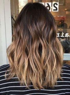 Mittellange Balayage Haare, dunkelbrauner Haaransatz und blonde Spitzen, gestreifte Bluse