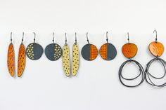 Handmade silver and enamel earrings using traditional techniques and contemporary and unique design. Yellow, orange, blue, grey with oxidised and satin finishes