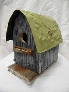 Barn birdhouse painted grey and white adorned with an antique ceiling tin painted green.  Functional.. $49.99, via Etsy.