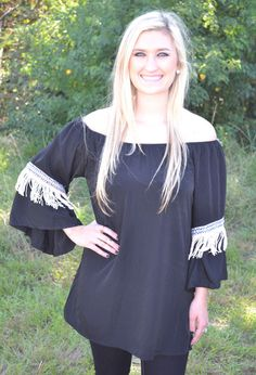 BLACK TUNIC WITH FRINGE DETAIL  34.00 Off the shoulder tunics are always a hit. This one features an aztec pattern with fringe detailing on the sleeve. Pair this top with your favorite skinny jeans or comfy leggings and booties to complete your look.