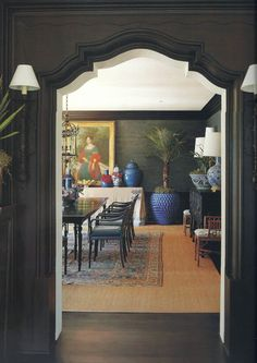 Dark walls, carved doorway, sconces, brass accents - looking into a dining room with grasscloth, old rug over sisal and blue accents - Mary McDonald Architecture Details, Interior Architecture, Rooms Ideas, Mary Mcdonald, South Shore Decorating, Indochine, Dark Walls, Top Interior Designers, Interior Exterior