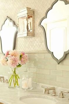 tile *** THIS is ABSOLUTELY BEAUTIFUL!  Adore the tile work, and the lovely shaped mirrors help show it off, they're not oversized, you get to see the beautiful tile and workmanship. The soft colors chosen , lantern light fixture in between - likely other light sources- maybe 2 more lanterns 1 on either side of the mirrors , overhead lighting, chandelier and/or  pot lights.
