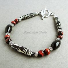 This is a tribal-inspired, stylish bracelet that I created for men. It features natural bone long pipe beads in black with distinctive tribal