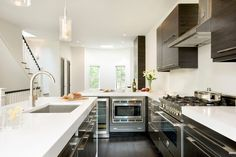 Fantastic sleek modern kitchen design with European kitchen cabinets, white quartz counter tops, ...
