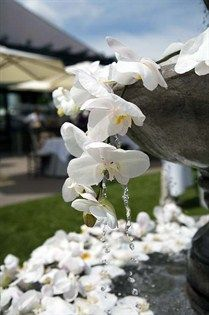 A second fountain overflows with crisp, white orchids.