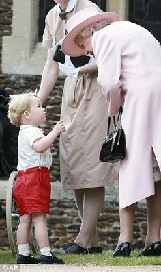 The Queen bends down to speak to Prince George...