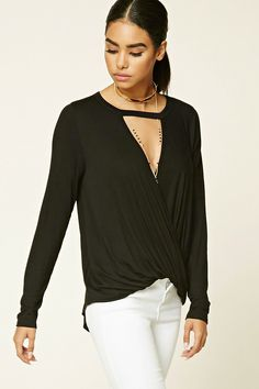 A soft slub knit top featuring a surplice cutout front, round neckline, long sleeves, and a high-low hem.