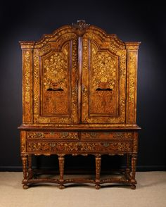 Buy online, view images and see past prices for An 18th Century Dutch Walnut & Floral Marquetry Cabinet on Stand. The upper section having two moulded panel doors inlaid with urns cascading flowers and butterflies, enclosing two shelves and five small drawers, beneath a shaped dome topped pediment with carved central crest. The base housing four drawers standing octagonal tapering legs united by shaped peripheral stretchers and terminating on bun feet, 101 ins (256 cms) high, 72 ins (183 ...