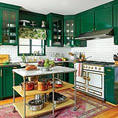 This industrial island is a sleek addition to the colorful kitchen. Brass knobs on the legs of the island compliment the hardware throughout the kitchen. | SouthernLiving.com