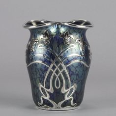 An excellent deep blue Art Nouveau glass vase with petrol blue iridescent finish and applied with an Art Nouveau motif silver overlay and wavered silvered rim.