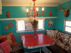 Pink travel trailer complete with chandelier and leopard print deer antlers.