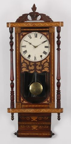 """19th century Continental marquetry inlaid regulator clock, with a carved leaf pediment above the clock face, flanked by turned pilasters, terminating in a inlaid scroll-like base, 38.5""""h x 15""""w x 5.5""""d."""
