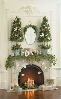 i love the (silver) pillar candles in the fireplace and the hanging stars around it.  plus the topiary type xmas trees.  also the use of just three colors: green, white and silver.