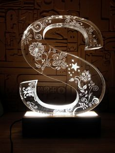 Yael Man designed S for shira. custom made letters design from plexiglass with a wooden stand and LEDs lighting.