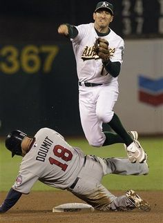 Oakland Athletics second baseman Adam Rosales throws to first over Minnesota Twins' Ryan Doumit (18), completing a Triple Play hit into be Trevor Plouffe in the fifth inning of a baseball game Tuesday, Aug. 21, 2012