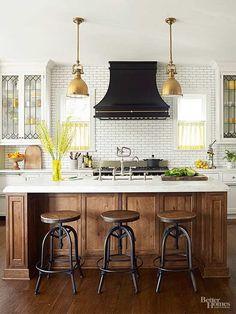 Black range hood with wood island. Ways to Warm Up Industrial Style - Mix up your metals using warm coppers, golds, and shiny silvers. Brass light fixtures cozy up this industrial kitchen and contrast with a nickel faucet and oil-rubbed bronze barstools. Home Decor Kitchen, New Kitchen, Home Kitchens, Kitchen Tile, Warm Kitchen, Kitchen Countertops, Kitchen Black, Kitchen Ideas, Wood Kitchen Island