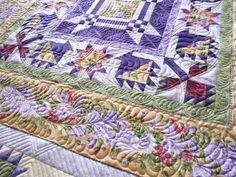 gorgeous sampler-style quilt with feathered borders