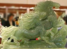 This jade carving is exceptional because of the fine workmanship of the horse's manes. In many places, the carving is apazingly thin and it lets the light shine through. It appears that this piece of jade naturally was of a lighter color in places, which the artist utilized beautifully in the horses' tail.