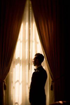 A portrait of a groom by the window. Photo by Justin Mott/Mott Visuals Weddings. Destination Wedding Photography Worldwide.