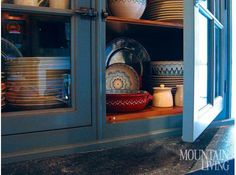 Kitchen cupboard, military blue cabinets, earthenware dishes, pottery RESIDENTIAL DESIGN by Lacroix Design INTERIOR DESIGN by S.B. Long Interiors PHOTO by Bryan Rowland & Susan Bednar Long MORE INFO at: http://www.mountainliving.com/article/refined-rustic#