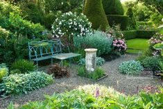 Formal garden with blue painted wrought iron bench, old sundial, gravel paths, roses, herbaceous perennials and view to lawns with box hedging and Yew topiary - Cerne Abbas, Dorset