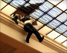 Life Falling Through the Cracks: An employee of the Greek Parliament hangs after falling through the glass roof over the Greek Parliament Hall