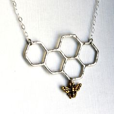 Silver Honeycomb Necklace by Rachel Pfeffer. An elegant honeycomb design is featured on this handmade necklace. Made from sterling silver, the design includes a sweet gold-plated bee. The pendant hangs from a 16-inch sterling silver cable chain, and is perfect for that sweetie pie you call Mom.