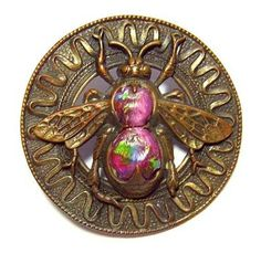 Victorian brass button with circular ring border which has been stamped with a ribbon design. In the open center is a winged insect with a Leo Popper glass body.