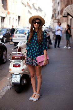 Shop this look on Lookastic:  http://lookastic.com/women/looks/hat-sunglasses-short-sleeve-blouse-clutch-skater-skirt-sandals/9549  — Khaki Straw Hat  — Dark Brown Sunglasses  — Navy and Green Polka Dot Short Sleeve Blouse  — Pink Leather Clutch  — Black Floral Skater Skirt  — Grey Horizontal Striped Canvas Sandals