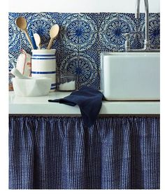 Nice mixture of patterned tile walls, solid towel and small patterned counter skirt along with solid whites of sink and counter.