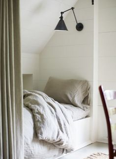 Simple but stylish room with bed built into eaves
