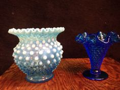 COLLECTIBLES FENTON TURQUOISE HOBNAIL VASE WITH A RUFFLED EDGE. IT ALSO HAS AN OPALESCENT COLOR TO IT AND STANDS 6 IN. TALL. ALONG WITH IT IS A DARK TURQUOISE VASE WITH A FLARED RUFFLE EDGE AND MEASURES 4 IN. TALL.
