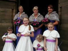the brides maids all showing off cerise and purple hand tied bouquets. and the younger flower girls with their flower wands