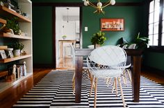 A striped IKEA rug adds contract to the bold green walls in the dining room. The dining table end chairs are from AllModern.
