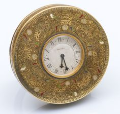 CARTIER Indian Clock round shaped carved brass, enamel decorated with scenes of animals and foliage. White Arabic dial, bearing the Cartier signature, and fleurdelisé needles. In its case at the Cartier shape.