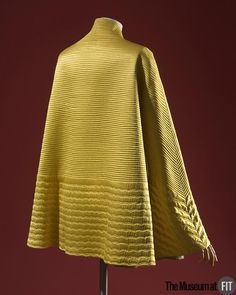 Jacket (back view) | Designer: Jeanne Lanvin (French, 1867-1946) | Yellow silk satin, silver lamé, and chartreuse wool | France, 1937 | The 1931 Paris Exposition promoted a coloniale moderne style that greatly influenced fashion, as in the color, shape, and embellishment of this evening jacket, reflecting a diffused Southeast Asian inspiration. Lanvin used machine-stitched quilting to create a surface decoration that is both modern and exotic | The Museum at FIT