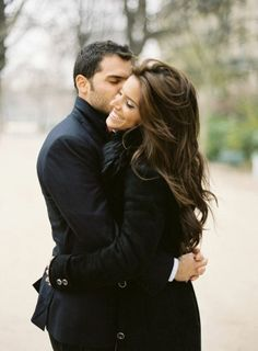 Gorgeous couple in black coats with dark hair kissing. Romance, fall.
