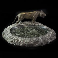 "DESCRIPTION:Magnificent large green marble ashtray garnished with a Vienna bronze fierce tiger figurine. Cut from natural marble with uncut edges and a smooth concaved green marble center bowl. CIRCA:Early-Mid 20th Ct. ORIGIN:Austria DIMENSIONS:H:6"" L:16.5"" W:14"""