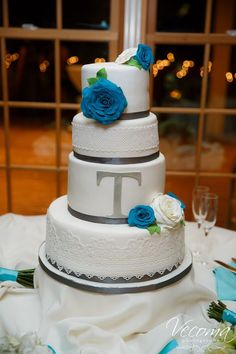 Beautiful 4-tired wedding cake with white and blue roses and a fine lace detail