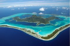 """Bora Bora's main island sits like a jewel in the center of its legendary multi-colored lagoon, which is surrounded by offshore islets inside a protective necklace of coral. The view the island from the window of an Air Tahiti flight has been compared to that of """"a tiny emerald in a setting of turquoise, encircled by a protective necklace of sparkling pearls""""."""