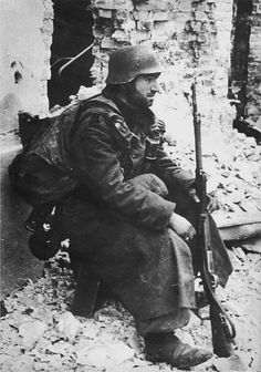 An exhausted German infantryman takes a break between firefights in the necropolis of Stalingrad. He is weighed down by a backpack most likely containing all his belongings. His severest problem is food and ammunition, both in extremely short supply once the Soviet encirclement tied the noose Oct-Nov 1942.