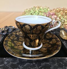 Elegant Aynsley corset teacup and saucer! A beautiful black and white corset teacup and saucer with fabulous gold leaves. Bone China - c. 1930s. Very good vintage condition – no chips, cracks, crazing or repairs. Gold gilt is in very good condition. Teacup: 2 3/4 tall x 3 1/2 across